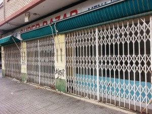 A closed down shop with graffiti on the walls