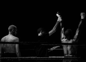 The referee holds up the winners hand after a boxing match