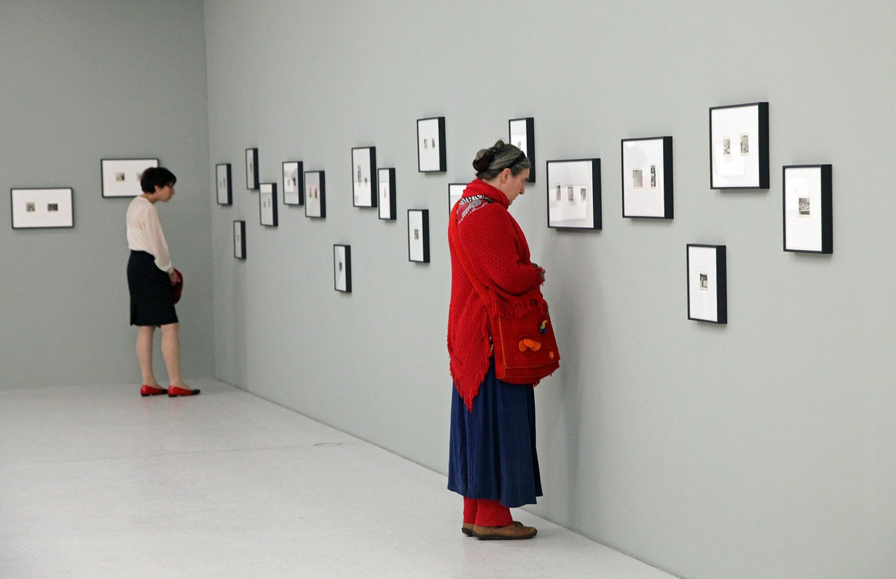 A woman closely examining a picture in a gallery